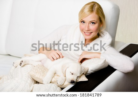 Woman sitting on the white leather sofa with sleeping on the pillow white puppy - stock photo
