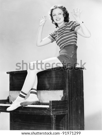 Woman sitting on top of a piano waving her arms