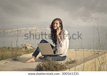 Woman sitting outdoors doing a phone call and using a pc