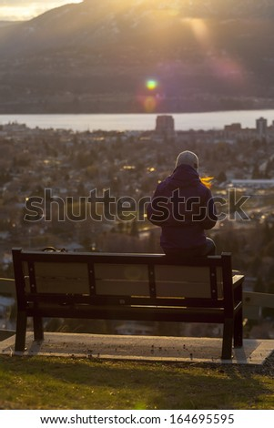 Woman Sitting Overlooking The City at Sunset  - stock photo