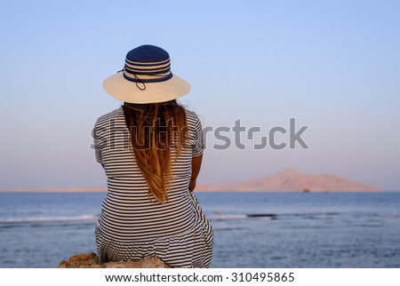 Woman sitting overlooking the ocean on a calm summer evening enjoying a tranquil sunset , view from the back of her looking to the right - stock photo