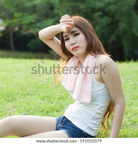 Woman sitting tired after jogging. Located on the lawn in the park.