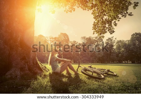 Woman sitting under sun light at day near her bicycle in the park - stock photo