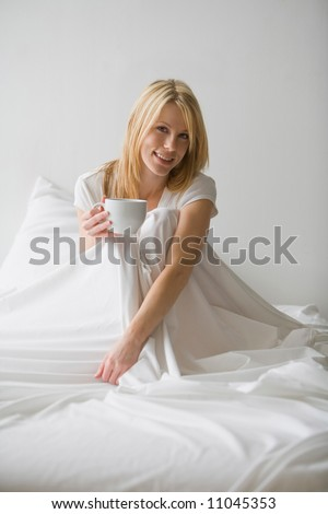 Woman sitting up in bed with white covers around her holding a cup - stock photo