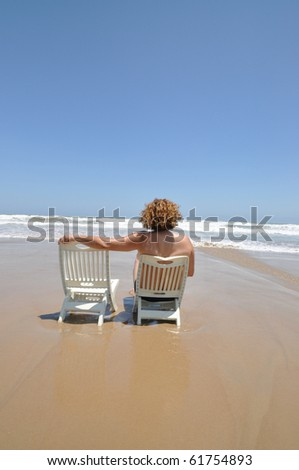 Woman sitting  watching waves roll in on Tropical Beach - stock photo