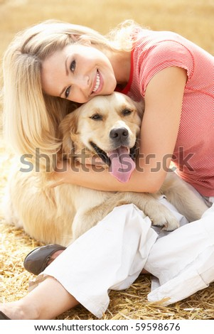 Woman Sitting With Dog On Straw Bales In Harvested Field - stock photo