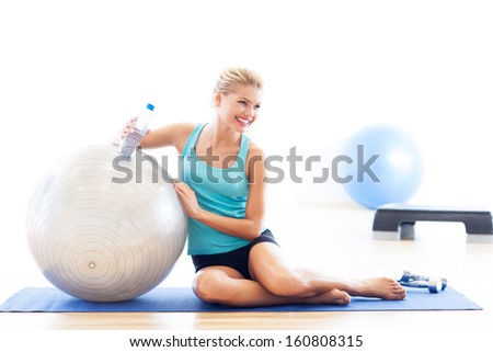 Woman sitting with fitness ball - stock photo