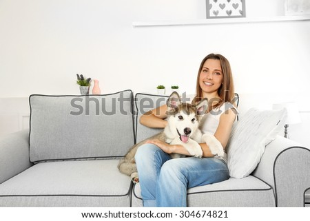 Woman sitting with her malamute dog on sofa in room - stock photo