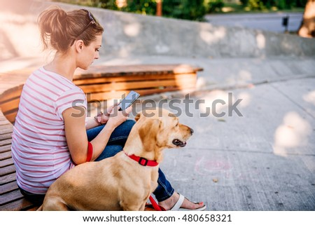 Woman sitting with the dog in the park and using phone