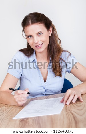 Woman sitting writing on a sheet of paper at a wooden table with distinctive grain