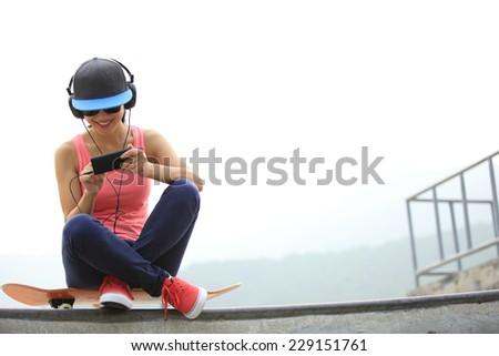 woman skateboarder listening music from cellphone mp3 player on skatepark  - stock photo