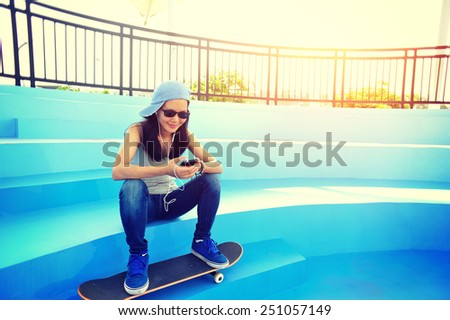 woman skateboarder sit on skatepark stairs listening music from smart phone mp3 player  - stock photo