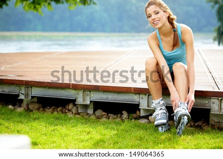 Woman skating in park. Girl going rollerblading sitting in grass putting on inline skates. - stock photo