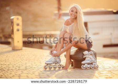 Woman skating in park. Girl going rollerblading sitting in grass putting on inline skates.  Caucasian woman in outdoor activities. - stock photo