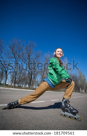woman skating with rollerblades in a park over blue sky. lower angle shot - stock photo