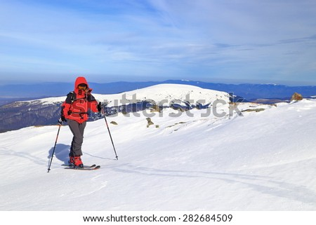 Woman skier climbs the mountain in sunny winter day - stock photo
