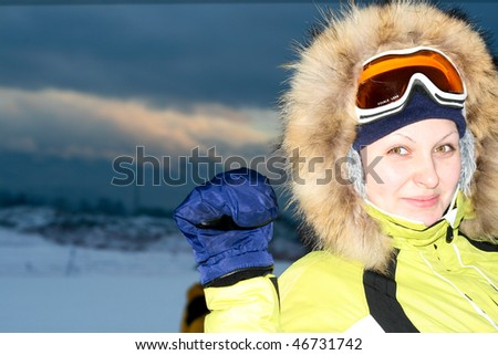 Woman skier portrait over cloudy mountains - stock photo