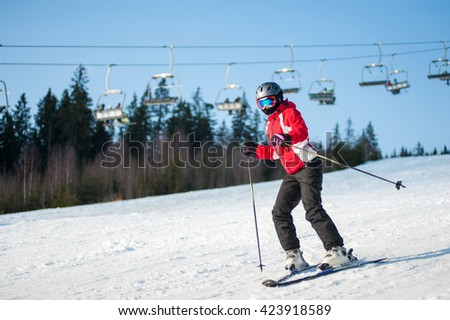 Woman skier skiing downhill at resort in sunny day against ski-lift, forest and blue sky. Woman is wearing red jacket, helmet and goggles. - stock photo