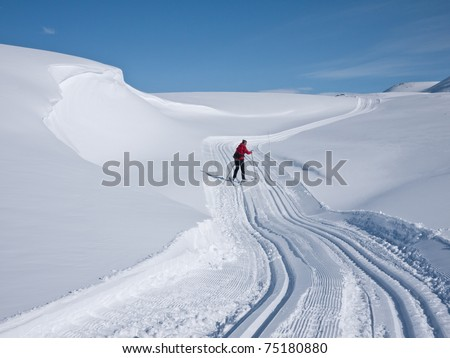 Woman skiing alone in a groomed curved double ski track with a characteristic wind swept snow formation on her left in the norwegian mountains at easter - stock photo