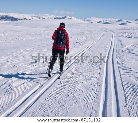 Woman skiing alone in a groomed double ski track heading towards some mountain summits in the norwegian mountains at easter - stock photo