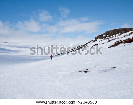 Woman skiing alone on a hillside at easter in the norwegian mountains - stock photo