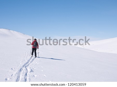 Woman skiing following a fresh ski track in the norwegian mountains at easter