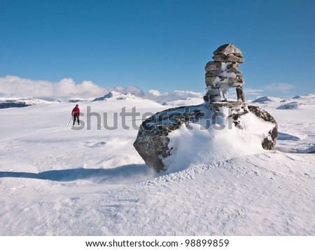 Woman skiing passing a cairn towards twin summits at easter in the norwegian mountains
