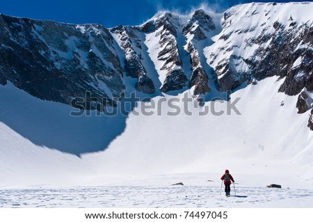 woman skiing to base of landry chutes on the north face of east mt sopris, an extreme ski descent in colorado - stock photo