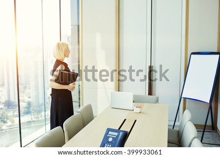 Woman skilled manager is reading presentation that she wrote for investors on flip chart with copy space for your advertising text message or promotional content, while is standing in conference room - stock photo