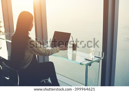 Woman skilled managing director is working on laptop computer with blank copy space screen for your advertising content, while is sitting in modern co-working space during her business trip in China - stock photo