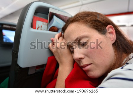 Woman sleep during flight aboard a jetliner airplane. - stock photo