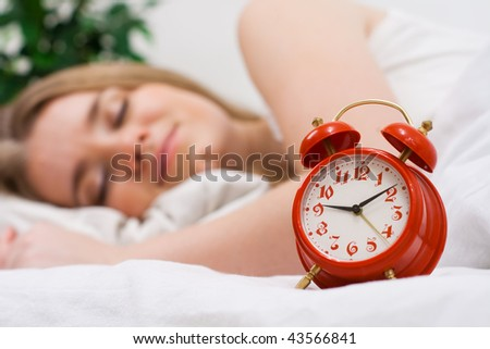 Woman sleep in bed with red alarm on foreground