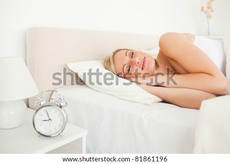 Woman sleeping and an alarm clock in her bedroom - stock photo