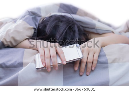 Woman sleeping and holding a mobile phone in the bed - stock photo