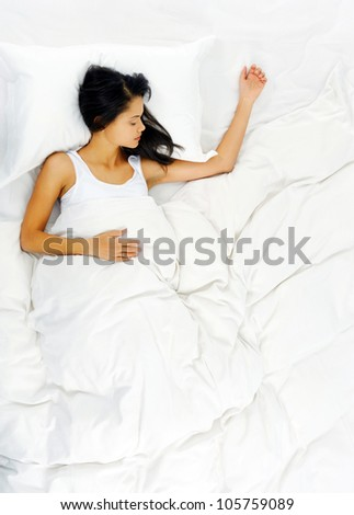 Woman sleeping and resting alone in her bed, dreaming. view from above - stock photo