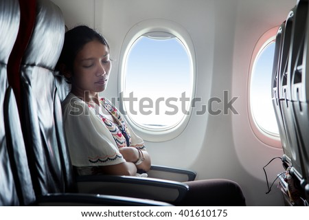 Woman sleeping in an airplane. Passenger relaxes at a window in a flying aircraft. - stock photo