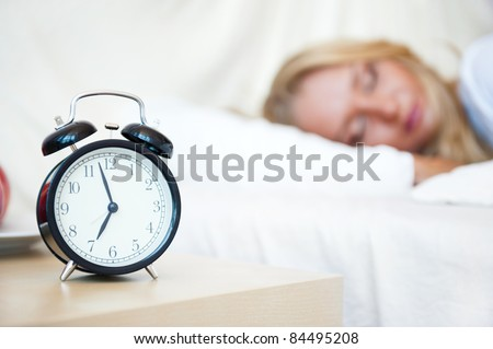 Woman sleeping in bed and alarm-clock (focus on alarm clock) - stock photo