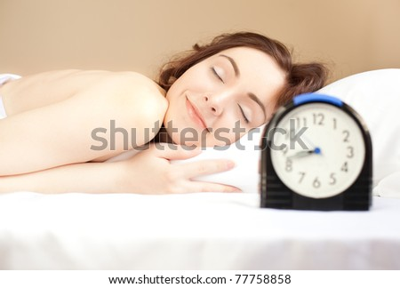 Woman sleeping in bed and alarm-clock  (focus on woman) - stock photo