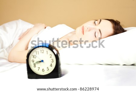 Woman sleeping in bed (focus on woman) - stock photo
