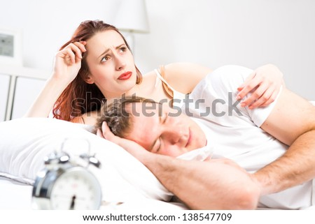 woman sleeping next to her husband in bed, relationship problems people - stock photo