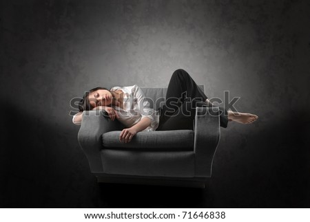 Woman sleeping on an armchair - stock photo