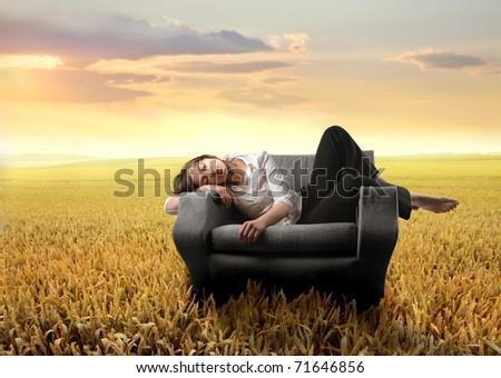 Woman sleeping on an armchair on a wheat field - stock photo