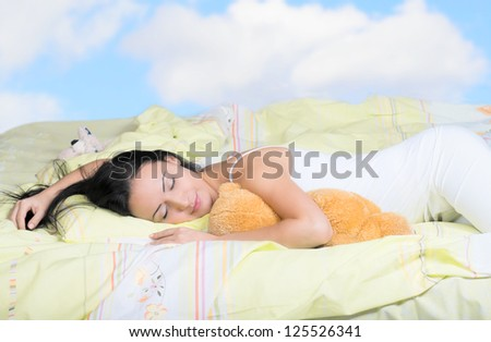 Woman sleeping on her side, cloudy sky background