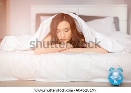 woman sleeping on her stomach covered by white coverlet. It is time to wake up  - stock photo