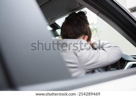 Woman sleeping on the wheel in her car - stock photo