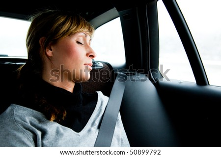 Woman sleeping relaxed and protected in car while driving in vacations - stock photo