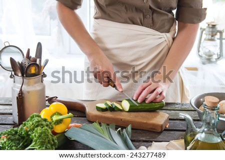 Woman slice zucchini on wooden table near window. Rustic style. - stock photo