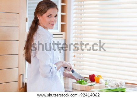 Woman slicing a pepper in her kitchen - stock photo