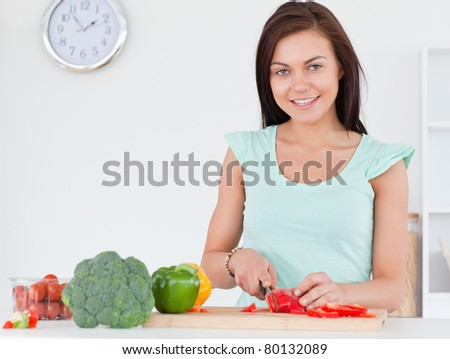 Woman slicing a pepper while looking at the camera in her kitchen