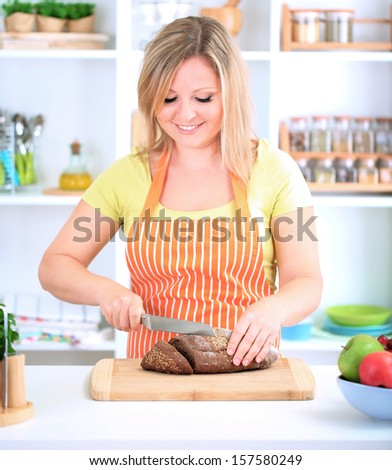 Woman slicing bread with sesame seeds on chopping board